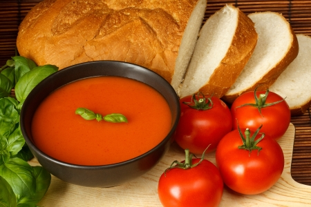 Bowl of tomato soup with basil garnish, in kitchen setting surrounded by ingredients Stock Photo - 14991828
