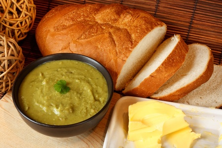 Bowl of homemade pea and ham soup in kitchen setting surrounded by crusty bread and butter Stock Photo - 14991838