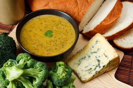 Bowl of broccoli and Stilton soup in kitchen setting surrounded by ingredients, crusty bread and butter Stock Photo - 14991826