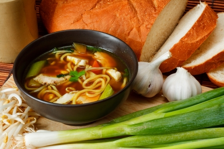 popular soup: chicken noodle soup a popular and favorite variety worldwide surrounded by ingredients and crusty bread