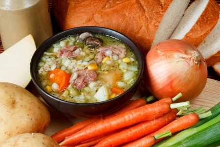 Bowl of ham broth in kitchen setting surrounded by ingredients, crusty bread and butter Stock Photo - 14991836