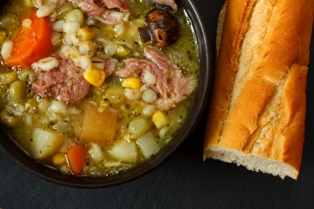 Bowl of ham stew with crusty bread photo