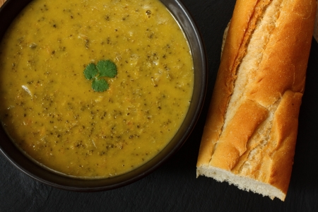 Bowl of broccoli and stilton soup in kitchen setting surrounded by ingredients, crusty bread and butter Stock Photo - 14991845