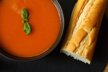 Bowl of tomato soup and basil garnish with bread baguette Stock Photo - 14991815