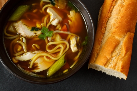 the popular comfort food of chicken noodle soup a favorite variety with crusty bread Stock Photo