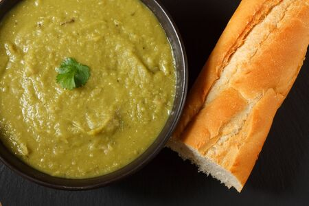 Bowl of homemade pea and ham soup iwith crusty french bread Stock Photo - 14991847