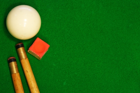 bar area: A green cloth billiards or pool table background with cues, cueball and chalk Stock Photo