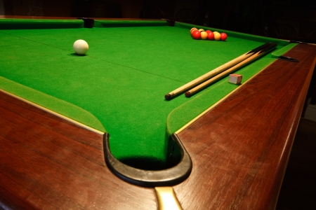 pool cues: A green cloth billiards or pool table with english league red and yellow balls Stock Photo