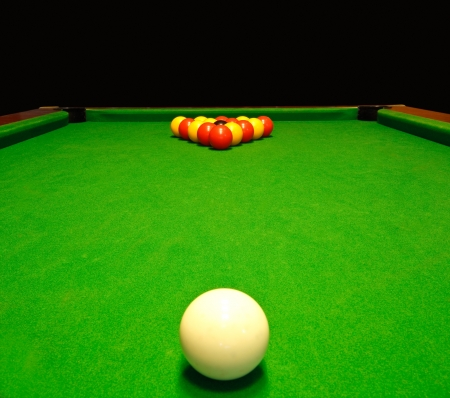 A green cloth billiards or pool table with english league red and yellow balls Standard-Bild