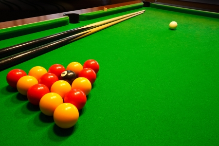 billiards tables: A green cloth billiards or pool table with english league red and yellow balls Stock Photo