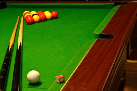 billiards cues: A green cloth billiards or pool table with english league red and yellow balls Stock Photo