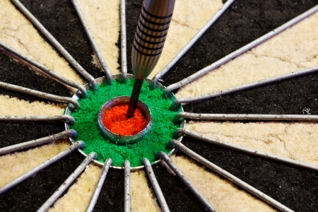 hits: a dart hits target in the centre of a darts board good business concept for success
