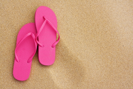 sandles: A Summer vacation background with a pair of sandals on beach Stock Photo