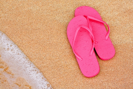 A Summer vacation background with a pair of flipflops on beach Stock Photo - 15840775