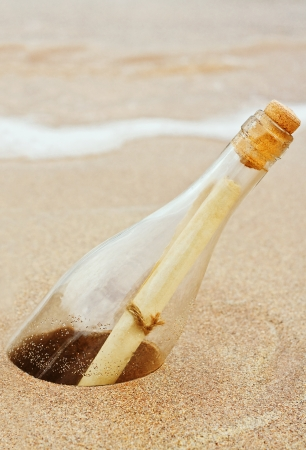a Message in a bottle buried in the sand at the coast a great business concept for direct mail, spam, or badly targeted communications including spam photo