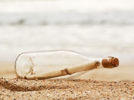 Mensagem em uma garrafa lavada em cima da praia, conceito do neg�cio excelente para correio, spam, ou comunica��o lenta ruim Imagens