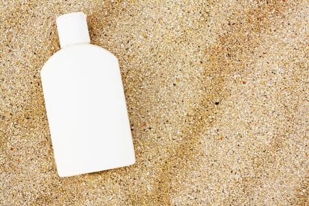 an unbranded bottle of sun block on the beach photo
