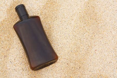 unbranded bottle of sun tan lotion on the beach photo