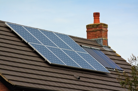 solar panel house: Photovoltaic Solar and central heating panels on tiled roof of residential home