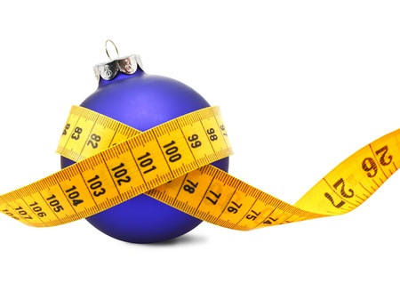'tape measure': Tape measure around a bauble concept symbolizing Christmas weight gain from eating too much food