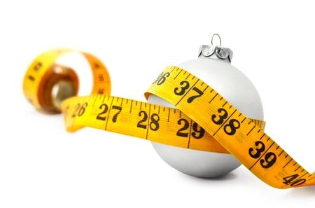 cinta metrica: Cinta métrica alrededor de un concepto chuchería de Navidad que simboliza la ganancia de peso por comer demasiados alimentos