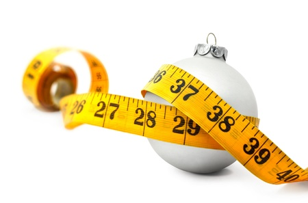 weight gain: Tape measure around a bauble concept symbolizing Christmas weight gain from eating too much food