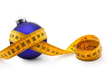 measure waist: Tape measure around a bauble concept symbolizing Christmas weight gain from eating too much food