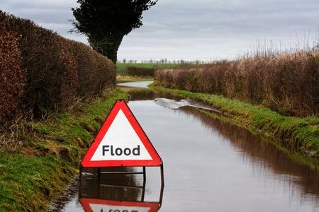 adverso: Flood se�al de peligro en un camino rural inundado muestra las condiciones adversas de manejo