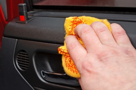 rag wheel: Cleaning the car door interior with yellow polishing cloth Stock Photo