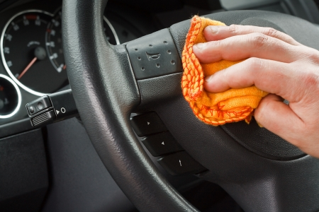 valet: polishing the car interior steering wheel with yellow duster