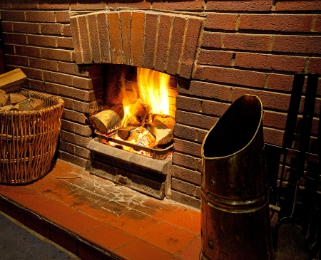 Cosy bright Roaring log fire with brick surround glowing with flames going up chimney Standard-Bild