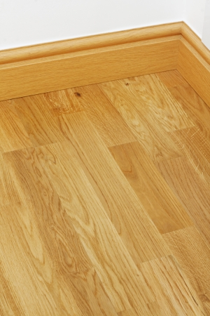 Close up showing some wood effect vinyl flooring and mdf imitation pine skirting boards in new build house photo
