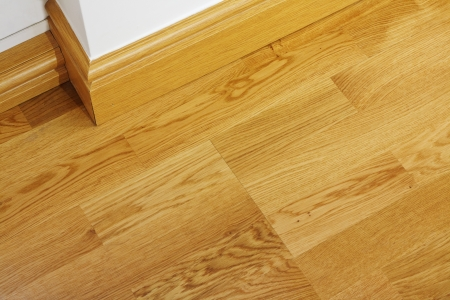 hardwood: Close up showing some laminate flooring and mdf imitation wood skirting boards in newly constructed house Stock Photo