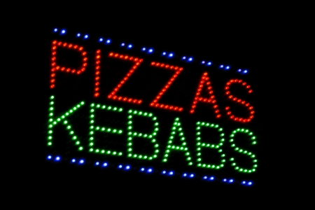 carry out: illuminated led sign advertising pizza and kebabs at take away or carry out
