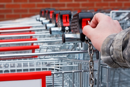 Inserting coin or token into shopping cart at the superstore