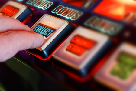 successful gambler collecting winnings from one armed bandit Stock Photo