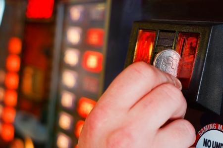 inserts: Gambler inserts dollar into slot machine