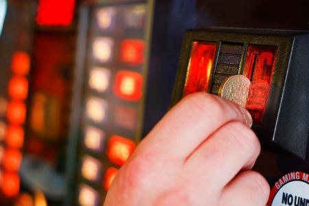 tragamonedas: Inserta Gambler libras moneda en la máquina de juegos de azar en el casino Foto de archivo