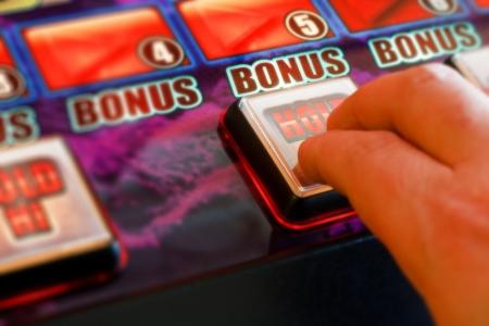 gambler playing a gaming machine at the amusement arcade Standard-Bild