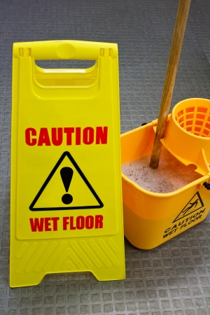 Caution wet floor sign with mop and bucket photo