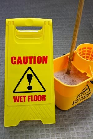 dweilen: Let op natte vloer teken met een mop en emmer