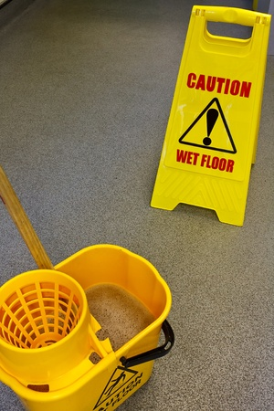 health and safety: Caution wet floor health and safety sign with mop and bucket Stock Photo