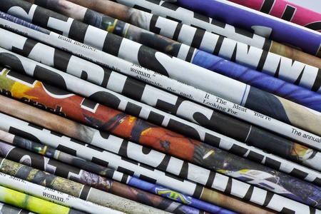 folded newspaper: close up on a pile of differnt color newspaper titles
