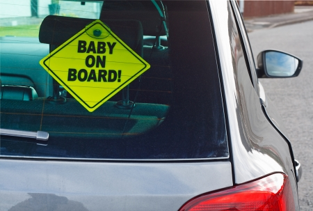 warning back: Baby on board warning sign in the back window of a car to advise cars behind of the presence of a toddler Stock Photo