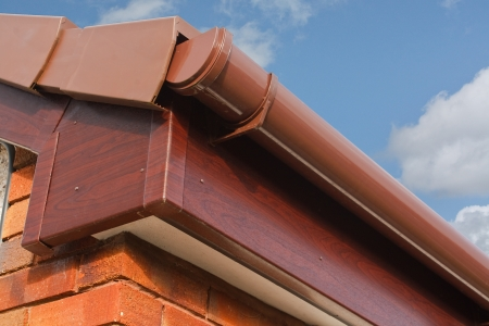 gutter: close up of Brown wood effect PVCu or plastic soffit, fascia and guttering on modern new build residential property Stock Photo
