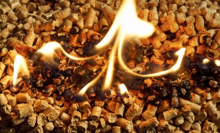 wood pellet: burning wood chip pellets a renewable source of energy becoming popular as a green environmentally friendly fuel for stoves which provide household heating