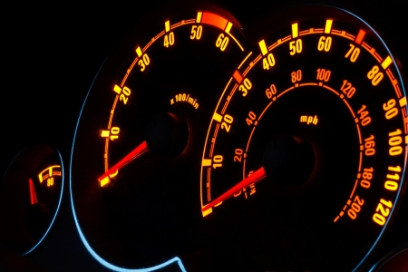 rev: Back lit Speedometer and rev counter dashboard dials illuminated at night in automobile Stock Photo