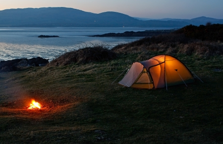 backpackers: Pitched nylon tent erected for camping vacation near the beach and coast