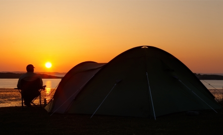 erected: sun sets on the horizon behind a camper sitting relaxing and enjoying his camping holiday creating a silhouette of the pitched tent with him sitting beside