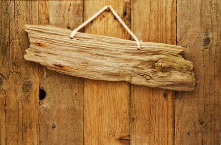 old grungy antique wooden plank of driftwood sign on string hung on aged wood door